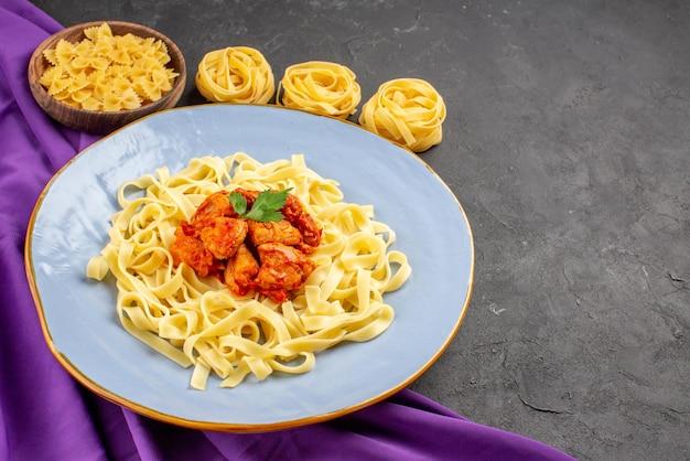紫色のテーブルクロスのさまざまな種類のパスタの横にあるプレートに肉汁と肉が入った肉汁の食欲をそそるパスタの側面クローズアップビューパスタ