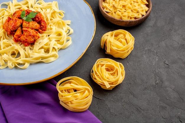 パスタのグレービーボウルと紫色のテーブルクロスにグレービーと肉が入った食欲をそそるパスタのプレートが付いた側面のクローズアップビューパスタ