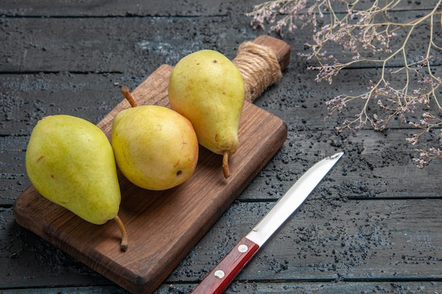 Side close-up view pears on board three green-yellow-red pears on cutting board in the center of dark table next to knife and tree branches