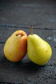 テーブルの上の側面のクローズアップビュー梨木製のテーブルの上の2つの熟した緑-黄-赤の梨