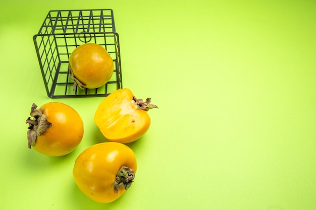Side close-up view persimmons basket with persimon next to the three appetizing persimmons