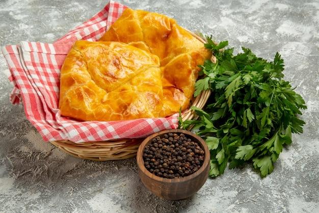 회색 배경에 파이와 식탁보가 든 나무 바구니 옆에 있는 검은 후추 허브 치즈 그릇의 측면 클로즈업 보기 파이와 레몬 접시