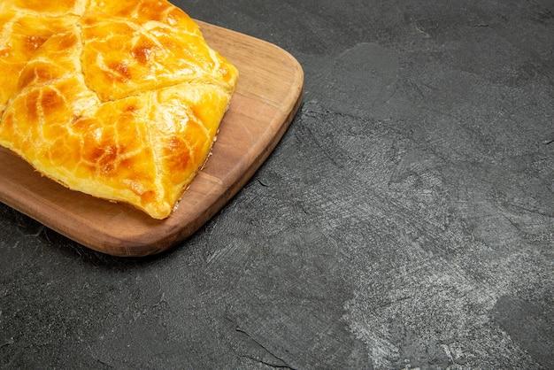 側面のクローズアップビューテーブルのパイ黒いテーブルの左側にある木製のキッチンボードのパイ