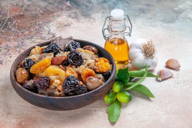 Side close-up view pilaf brown bowl of pilaf garlic oil citrus fruits