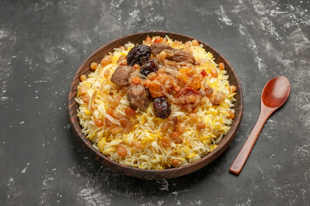 Вид сбоку крупным планом ложка плова, рисовое мясо и сухофрукты в миске