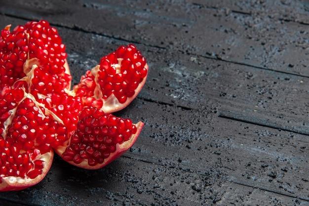Vista ravvicinata laterale del melograno in pilled melograno in pilled rosso appetitoso sul lato sinistro del tavolo grigio