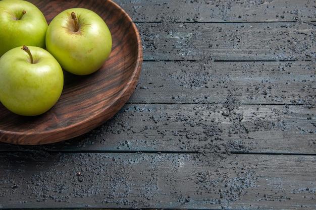 暗いテーブルの上の食欲をそそるリンゴのリンゴの茶色のプレートの側面のクローズアップビュープレート
