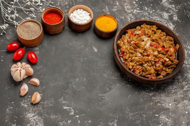 黒いテーブルの上のスパイスの木の枝とニンニクのボウルの横にあるトマトとサヤインゲンの豆プレートの側面拡大図プレート