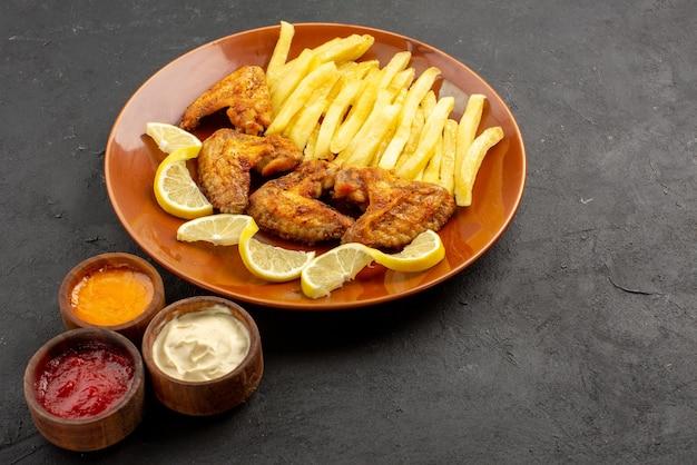 어두운 배경에 세 가지 유형의 소스를 곁들인 식욕을 돋우는 프렌치 프라이 치킨 윙과 레몬의 측면 클로즈업 보기