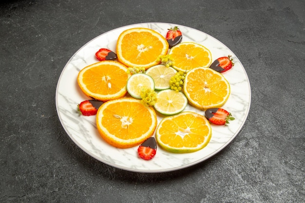 회색 테이블 중앙에 있는 다채로운 과일 초콜릿의 과일 접시의 측면 클로즈업 보기