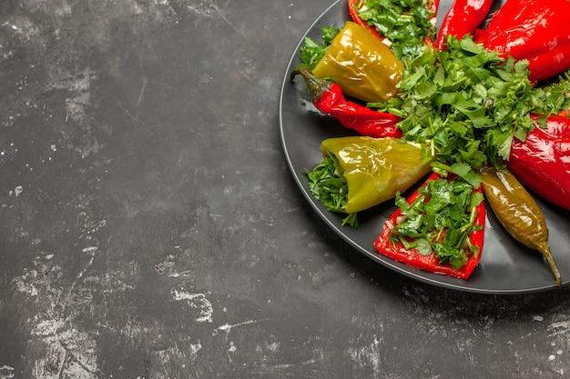 Боковой вид крупным планом перца черная тарелка аппетитного красного и зеленого перца с травами