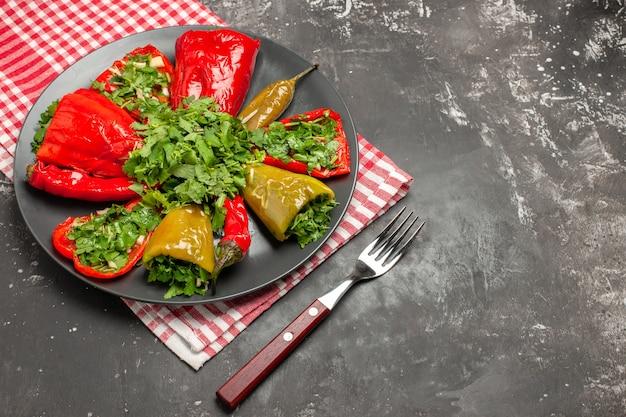 唐辛子の側面のクローズアップビュープレート市松模様のテーブルクロスフォークの唐辛子のプレート