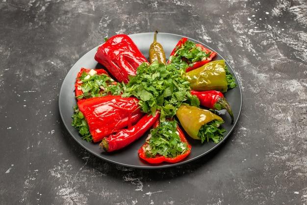 Piatto di vista ravvicinata laterale di peperoni peperoni con erbe sul piatto scuro