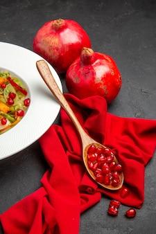 Vista ravvicinata laterale melograno insalata di verdure melograni cucchiaio con semi di melograno