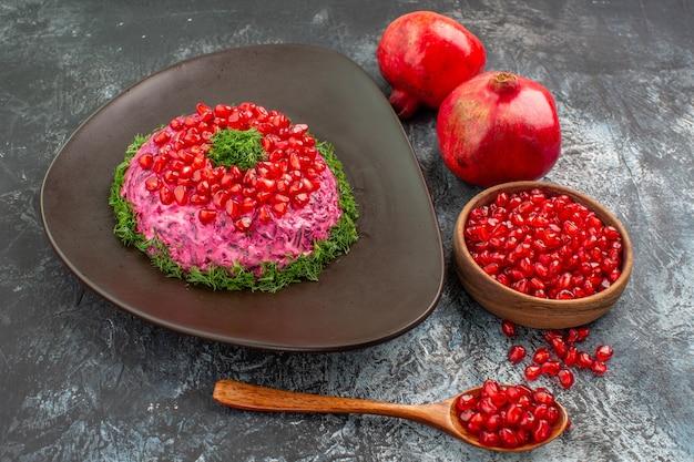 Гранаты сбоку крупным планом аппетитное блюдо миска с ложкой семян граната