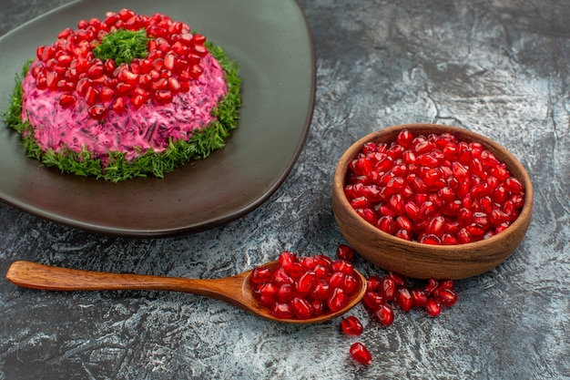 Side close-up view pomegranates dish of pomegranate herbs pomegranate seeds in the bowl spoon