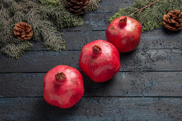 테이블 중앙에 원뿔이 있는 가지 옆에 있는 세 개의 빨간 석류