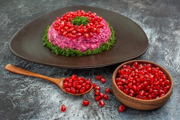 Vista ravvicinata laterale semi di melograni nel piatto cucchiaio ciotola di erbe di melograno
