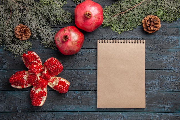 Side close-up view pomegranates on table pilled pomegranate next to two red pomegranates cream notebook and spruce branches with cones