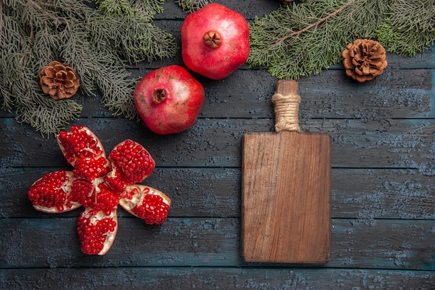 Side close-up view pomegranates on table pilled pomegranate next to two red pomegranates wooden board and spruce branches with cones