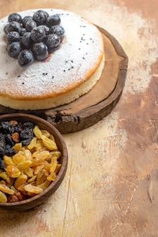 Боковой вид крупным планом изюм торт с виноградом на доске миску изюма