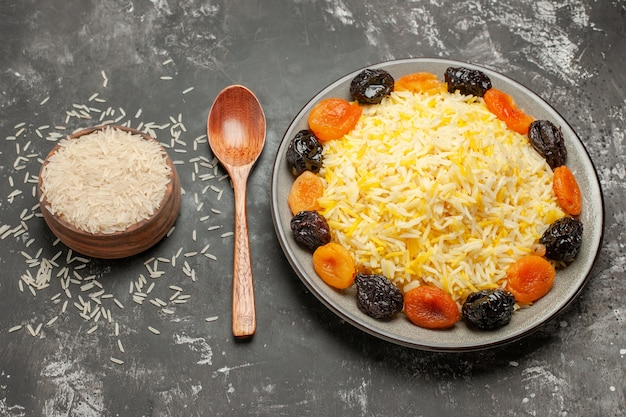 Side close-up view rice the appetizing rice with dried fruits spoon bowl of rice
