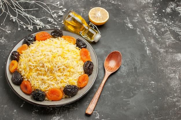 Вид сбоку крупным планом рис, лимон, ложка, бутылка масла, тарелка риса с сухофруктами