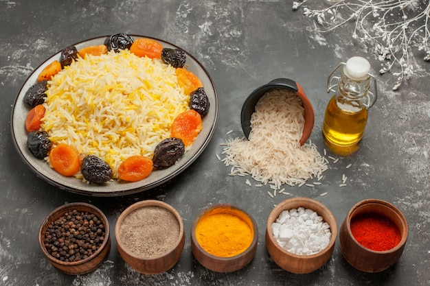 Side close-up view rice spices plate of rice with dried fruits bottle of oil bowl of rice