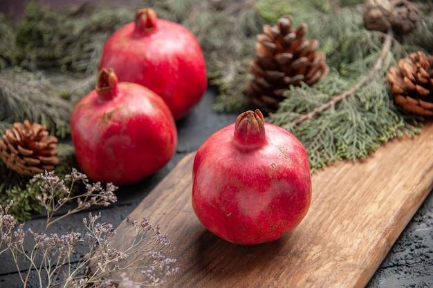 Vista ravvicinata laterale melograni maturi e rami melograno rosso sul tagliere accanto a due melograni e rami di abete rosso con coni sul tavolo grigio