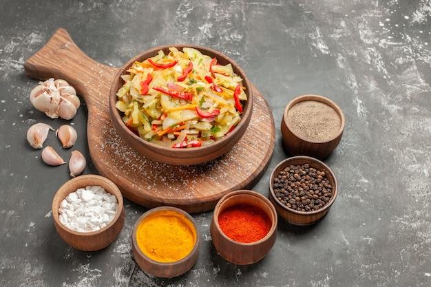 커팅 보드 마늘에 다채로운 향신료 야채 샐러드의 측면 확대보기 샐러드 그릇