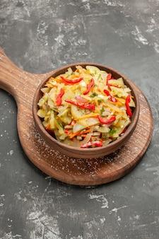 Vista ravvicinata laterale insalata di verdure insalata nella ciotola marrone sul bordo della cucina in legno