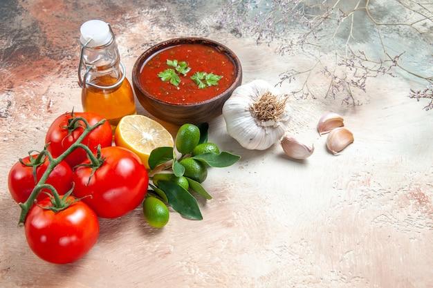 Vista ravvicinata laterale salsa pomodori con pedicelli bottiglia di olio salsa al limone aglio