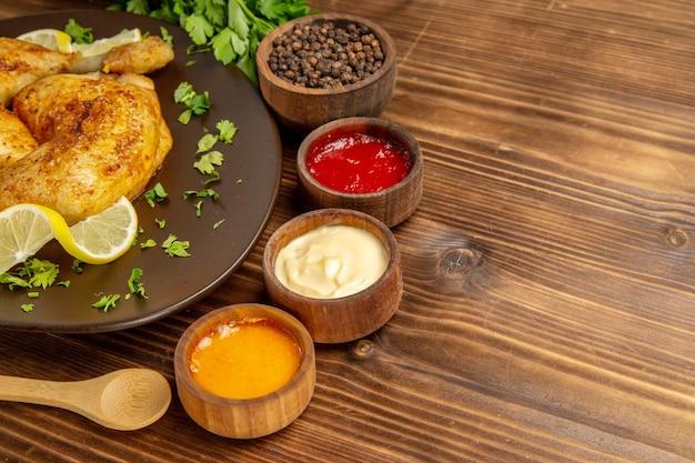 Боковой вид крупным планом соусы и куриная тарелка с курицей и лимоном рядом с мисками с тремя видами соусов и черным перцем и деревянной ложкой