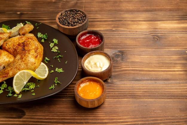 Vista ravvicinata laterale salse e ciotole di pollo di tre tipi di salse e pepe nero accanto al piatto di pollo con erbe e limone sul lato sinistro del tavolo
