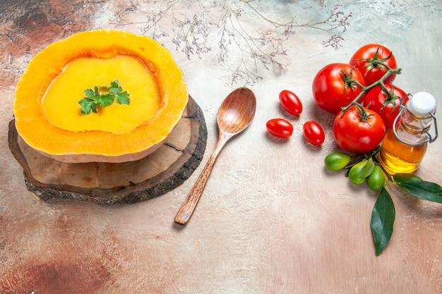 Vista ravvicinata laterale una zuppa di zucca minestra sulla tavola cucchiaio olio agrumi pomodori
