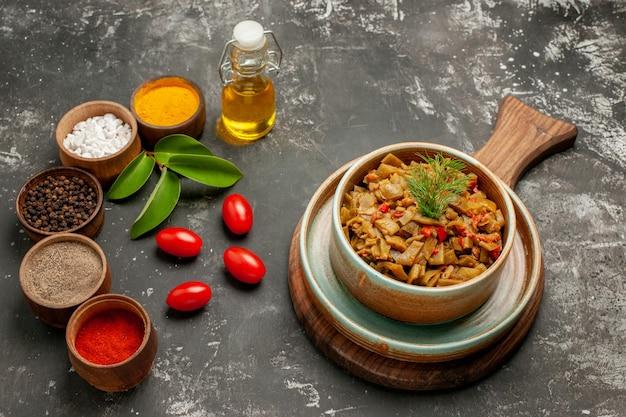 Vista ravvicinata laterale spezie e piatto di fagiolini e pomodori sul tagliere ciotole di spezie colorate foglie pomodori e bottiglia di olio sul tavolo