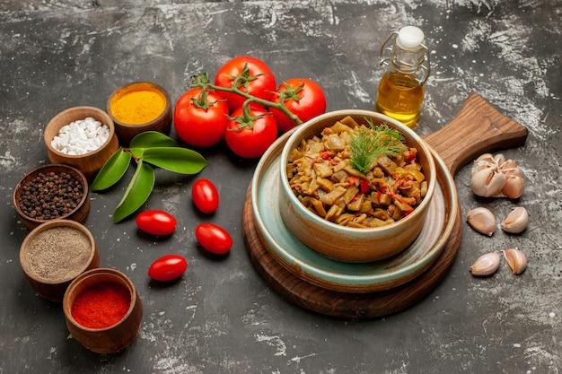 側面の拡大図まな板の上にトマトとサヤインゲンをスパイスカラフルなスパイスのニンニクボウルは暗いテーブルに油のペディセルボトルとトマトを残します