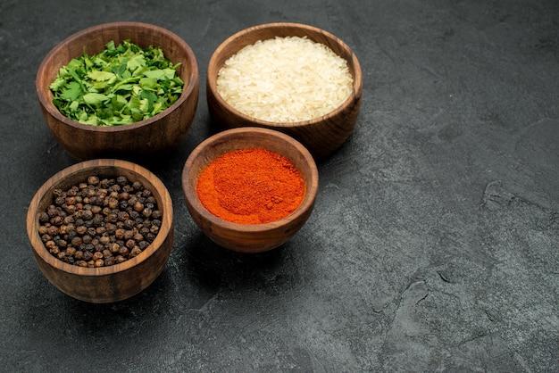 Боковой вид крупным планом специи на столе, травы, специи, рис и черный перец в мисках на левой стороне черного стола