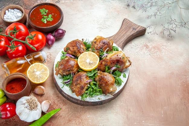 Vista ravvicinata laterale spezie spezie bottiglia di olio salsa di pomodori bordo con pollo limone erbe