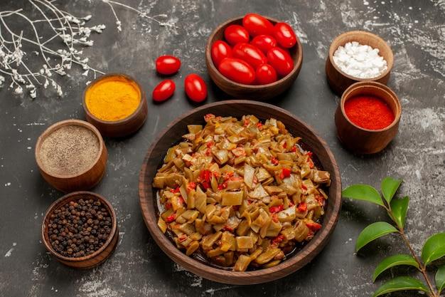 Vista ravvicinata laterale spezie sul tavolo spezie colorate pepe nero e pomodori nelle ciotole di legno accanto ai rami degli alberi e foglie sul tavolo grigio