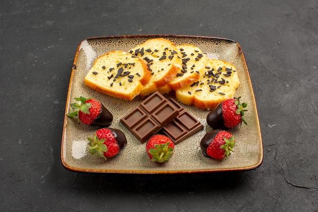 측면 클로즈업 보기 딸기와 케이크 식욕을 돋우는 초콜릿으로 덮인 딸기와 사각형 접시에 초콜릿이 있는 케이크