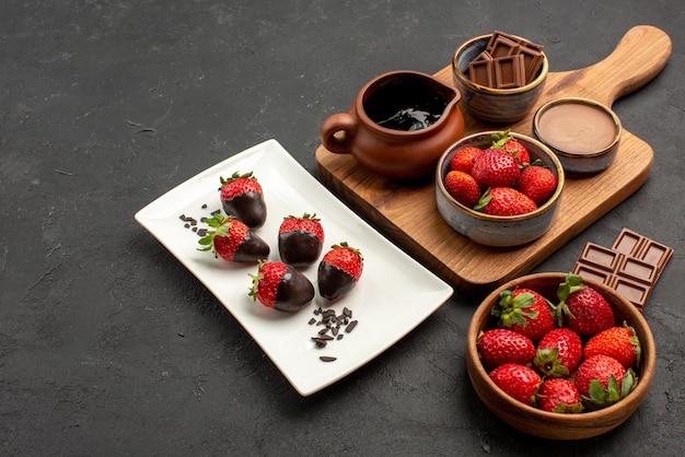 Vista ravvicinata laterale fragole appetitose barrette di cioccolato ciotola di fragole piatto di fragole ricoperte di cioccolato e tavola da cucina con crema al cioccolato e fragole