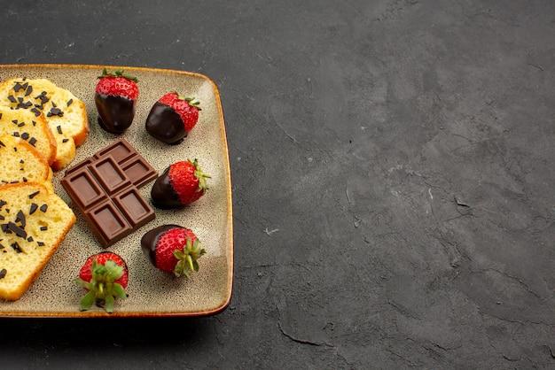 Vista ravvicinata laterale fragole e torta con fragole ricoperte di cioccolato al cioccolato su piastra grigia sul lato sinistro del tavolo