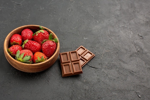 Вид сбоку крупным планом клубники в миске клубника в миске рядом с плитками шоколада на темном столе