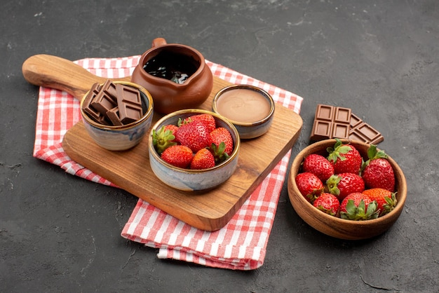 Side close-up view strawberries on tablecloth kitchen board with bowls of strawberries and chocolate on it and plate of strawberries and chocolate in the center of the table