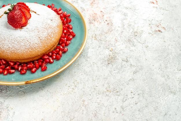 灰色のテーブルの上のイチゴとザクロと食欲をそそるケーキの側面のクローズアップビューイチゴザクロの青いプレート