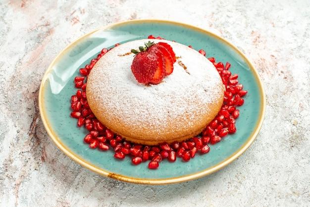 Vista ravvicinata laterale piatto di torta al melograno alla fragola con fragole e melograno sul tavolo grigio-rosa