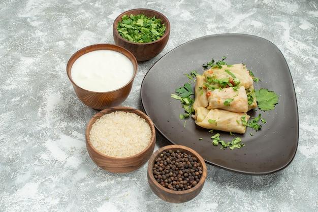 Vista ravvicinata laterale cavolo ripieno piatto grigio di cavolo ripieno accanto a ciotole di erbe panna acida riso e pepe nero sul tavolo