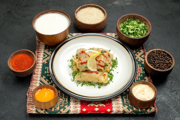 側面拡大図キャベツの詰め物ハーブのボウルの横にあるキャベツの詰め物白と黄色のソース黒胡椒スパイス米とサワークリームを色とりどりの市松模様のテーブルクロスに