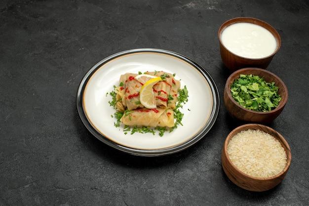 Vista ravvicinata laterale cavolo ripieno cavolo ripieno con erbe limone e salsa su piatto ed erbe riso e panna acida in ciotole sul tavolo nero